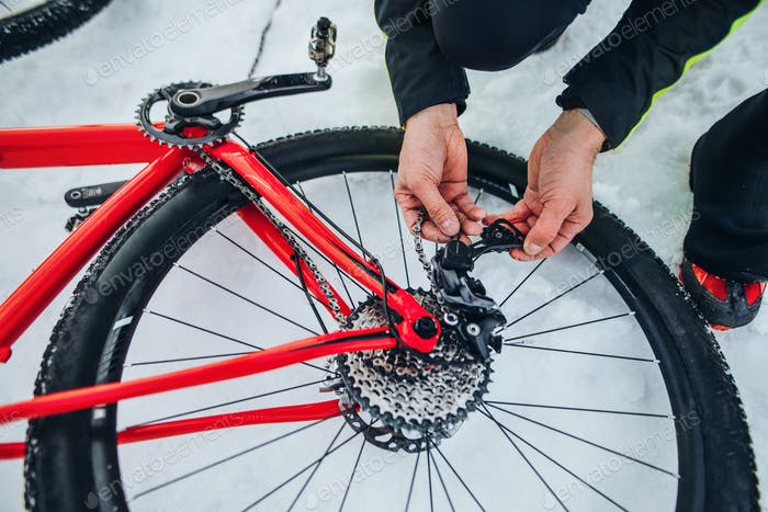 Midsection of mountain biker fixing bicycle outdoors in snow in winter
