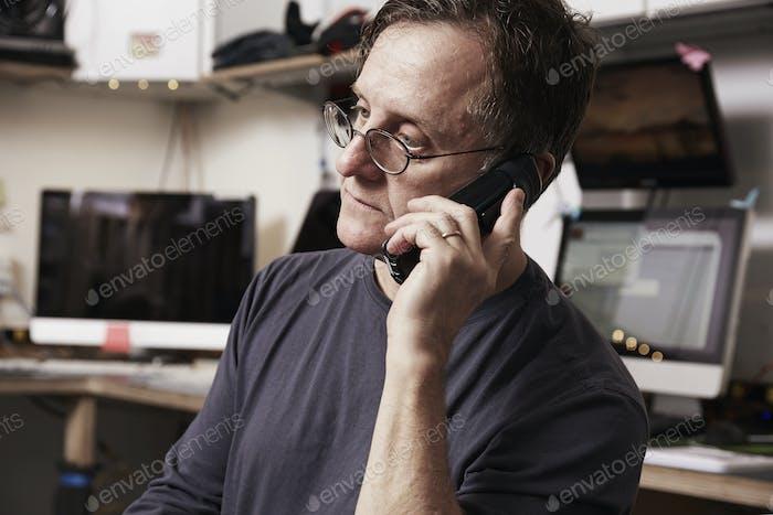 Ein Mann sitzt in einem Raum voller Computer mit einem Telefon an seinem Ohr.