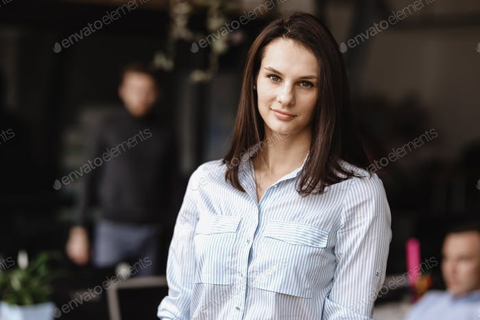 Young brunette girl dressed in office style clothes is standing in the modern office