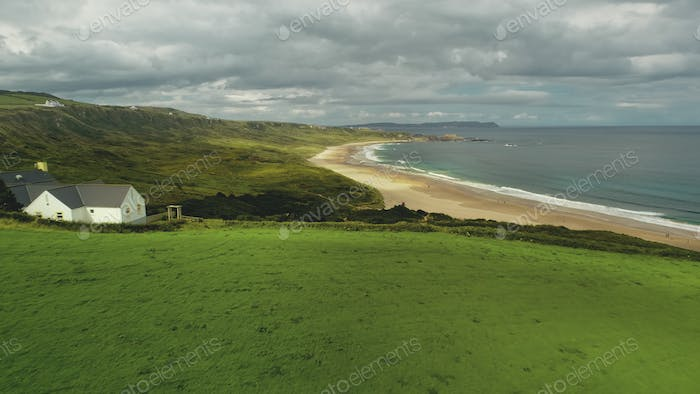 Beach lodge aerial shot: green meadow near sea bay and lonely White Rocks, Northern Ireland