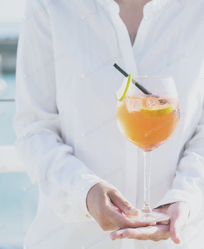 Woman with a glass of aperol spritz cocktail