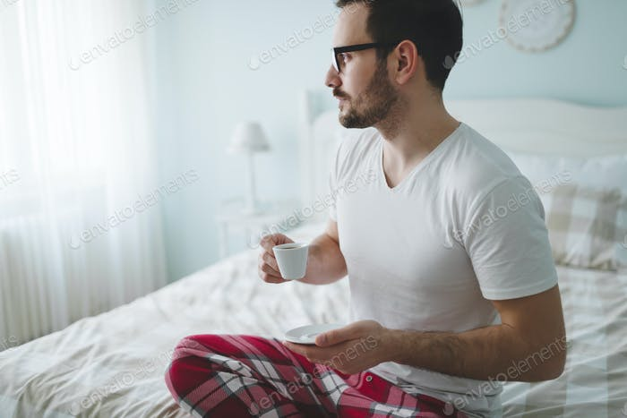 Mann im Pyjamas genießen Morgenkaffee