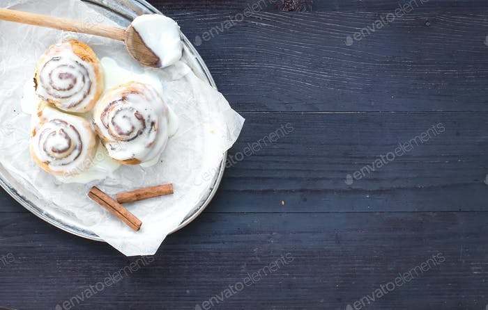 Cinnamon rolls with cream-cheese icing and cinnamon sticks on a