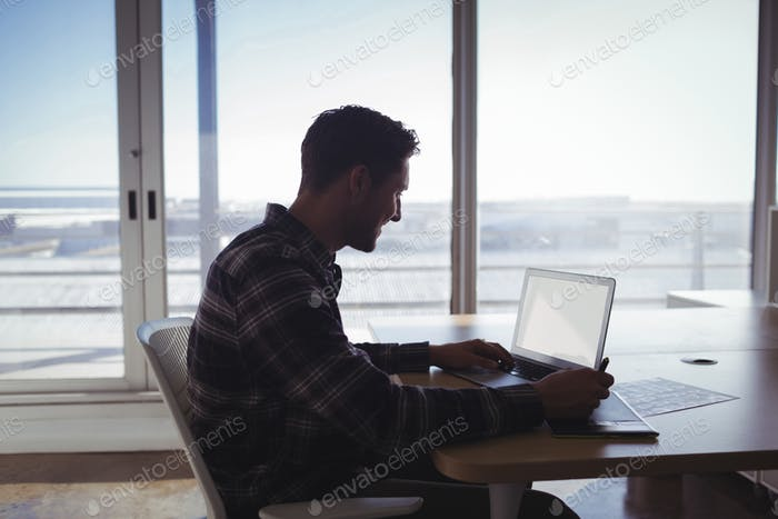 Young editor using digitizer and laptop on desk in office