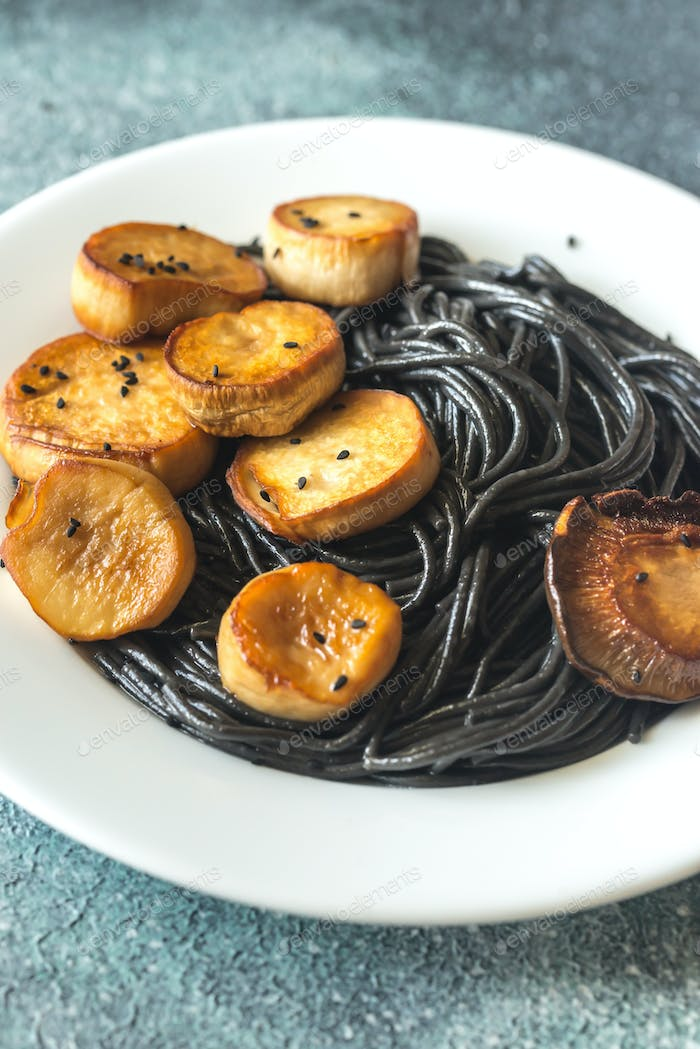 Portion of black pasta with king oyster scallops