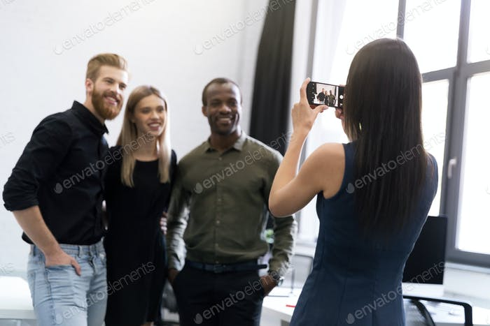Young lady and two young men getting their picture taken