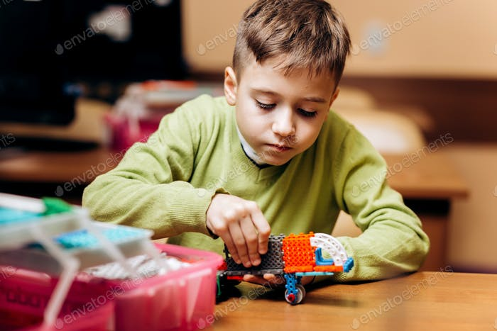 Boy dressed in green sweater sits at the table in the robotics school and makes a robot from the