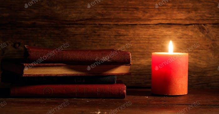 Vintage Bücher und eine Kerze auf Holzhintergrund