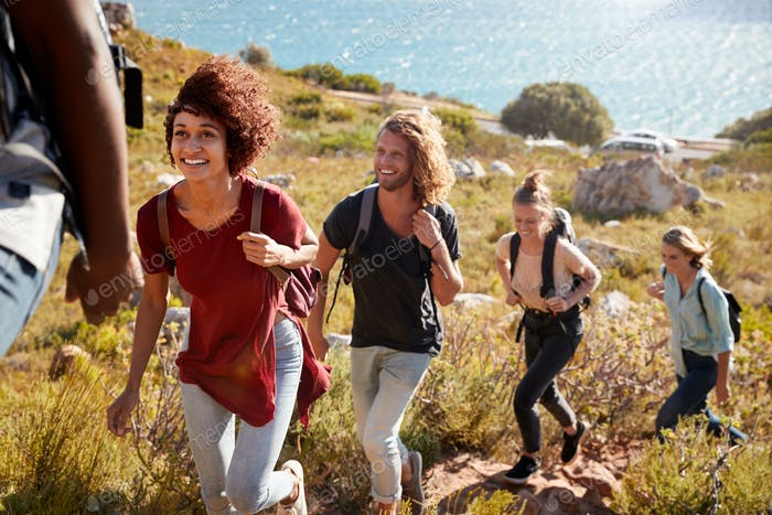 Happy young adult friends hiking single file uphill on a path by the coast, full length