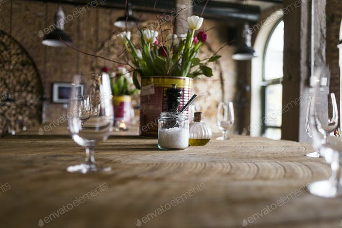 Surface level of condiments and flower vase on table in restaurant