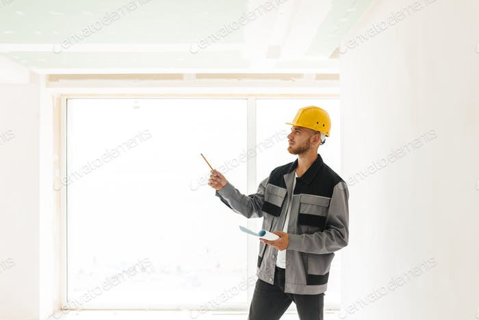 Thoughtful engineer in work clothes and yellow hardhat holding p