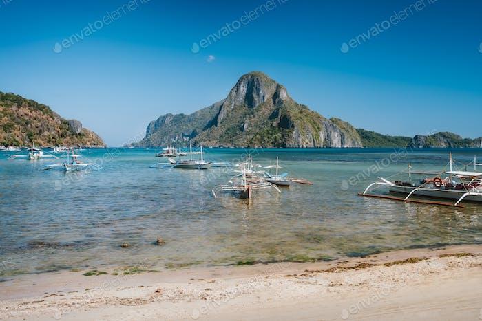 El Nido bay with island hopping boats. Cadlao island in background, Palawan, Philippines