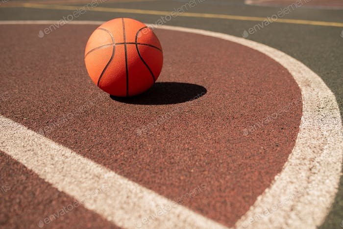 Ball for playing basketball lying on sports field or stadium