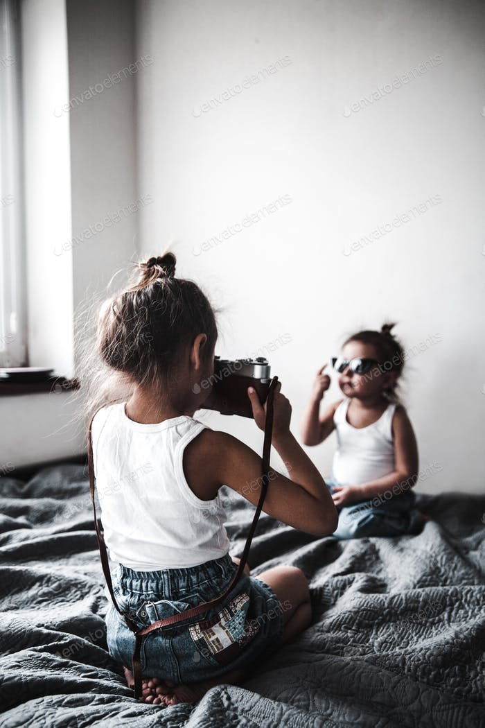 Two little girls taking a picture of each other. little women of fashion