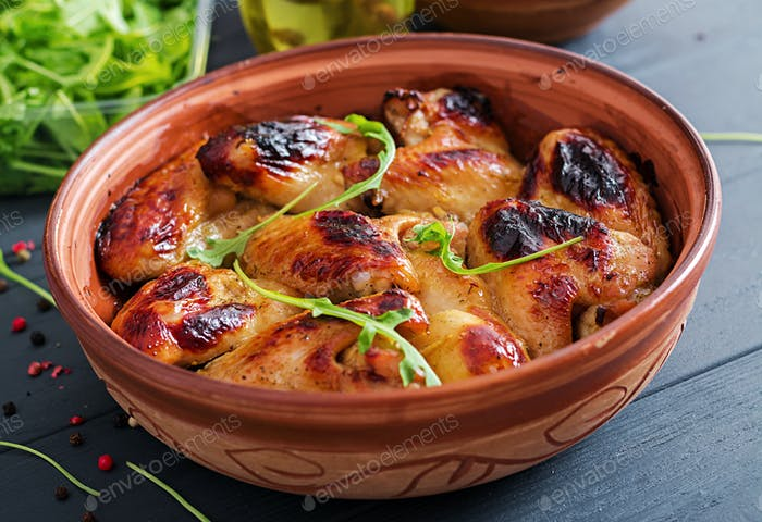 Baked chicken wings in bowl on wooden table.