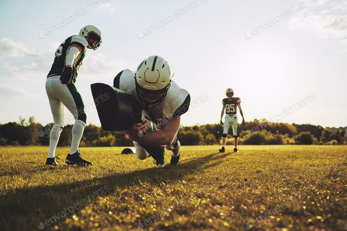 American football players doing tackling drills on a sports field