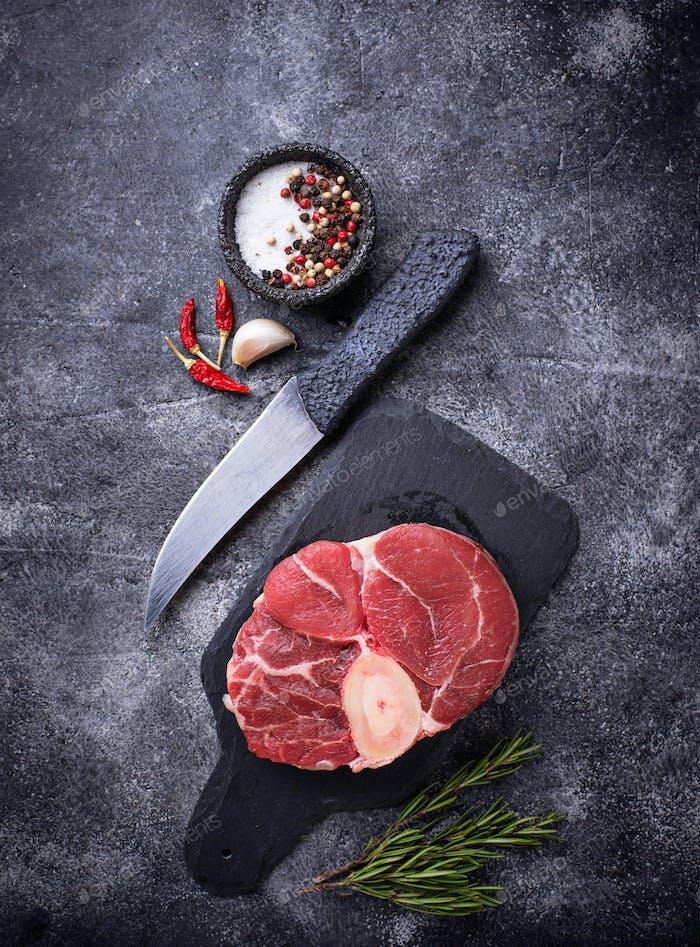Raw meat osso buco on slate cutting board