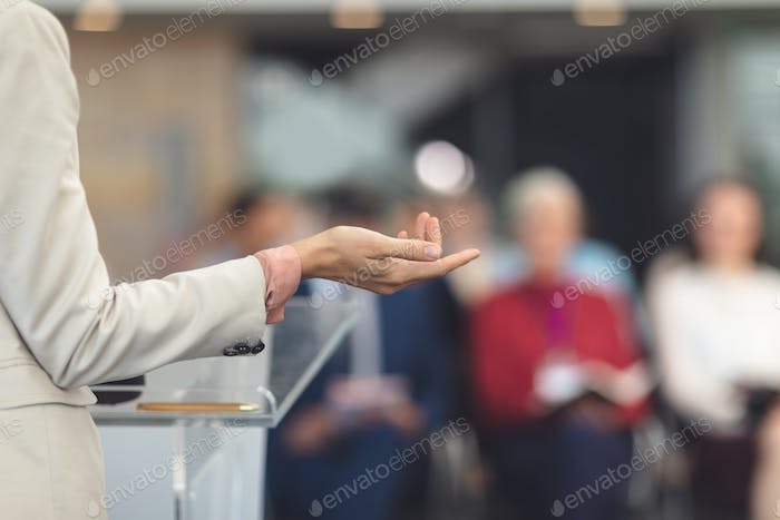 Mid section of mixed race female speaker speaking at a business seminar in modern office