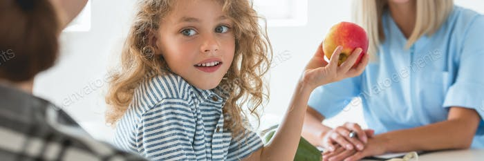 Little boy playing with fruit during a visit to a dietitian