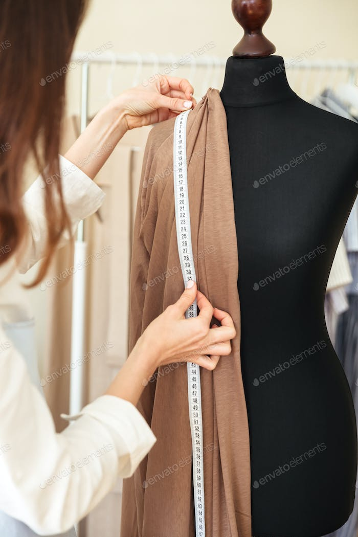 Cropped image of seamstress measuring fabric on black dummy