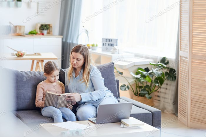 Adult Woman Reading with Daughter at Home