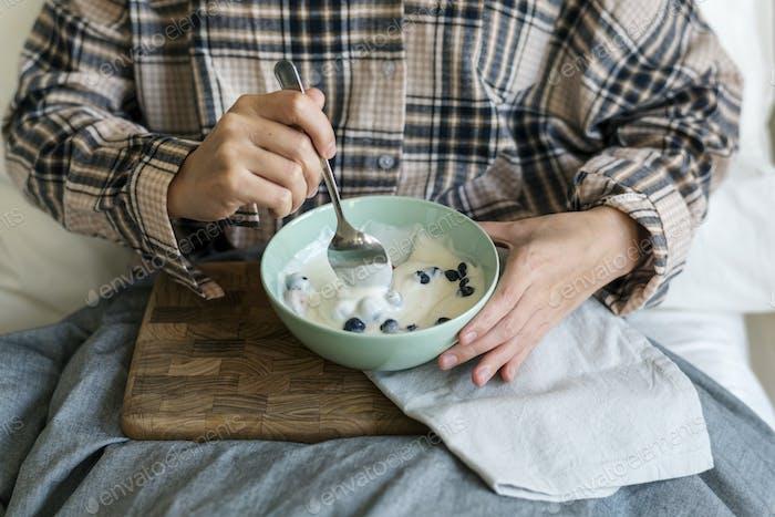 Caucasian girl eating yogurt on bed