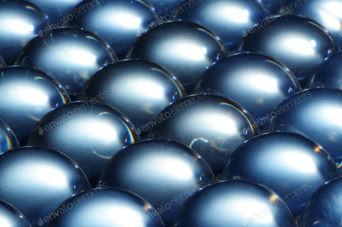 Close-up large steel balls lie next to each other