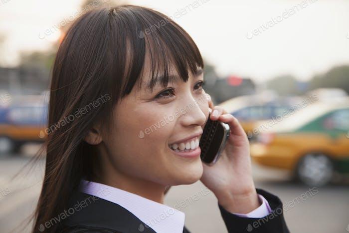 Junge Geschäftsfrau mit dem Telefon draußen auf der Straße in Peking, Nahaufnahme Porträt