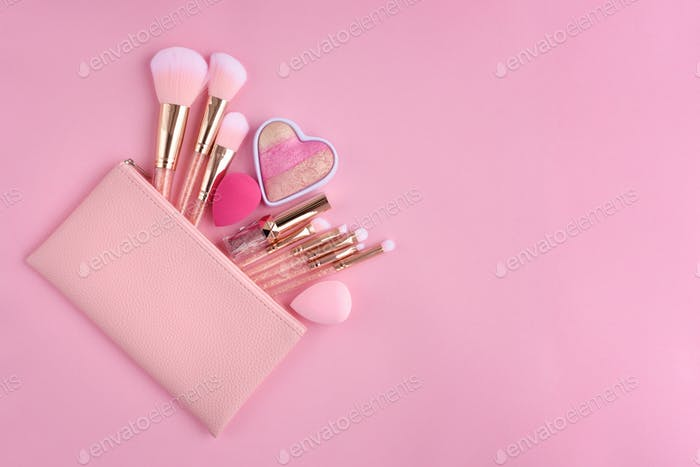 A pink cosmetics bag with make-up brushes and makeup products