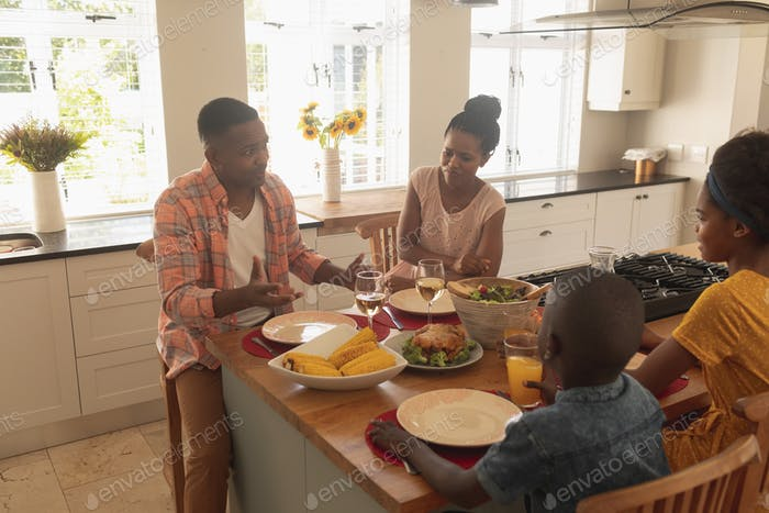 High angle view of happy African American family having food at dining table in a comfortable home