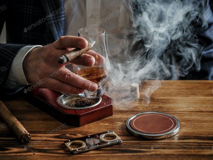Man at a bar drinks whisky and smokes a cigar
