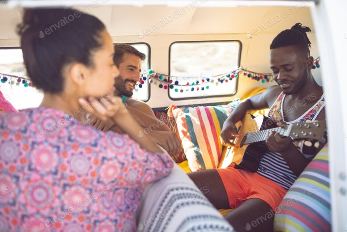 Closed-up of happy group of diverse friends having fun in a camper van at beach