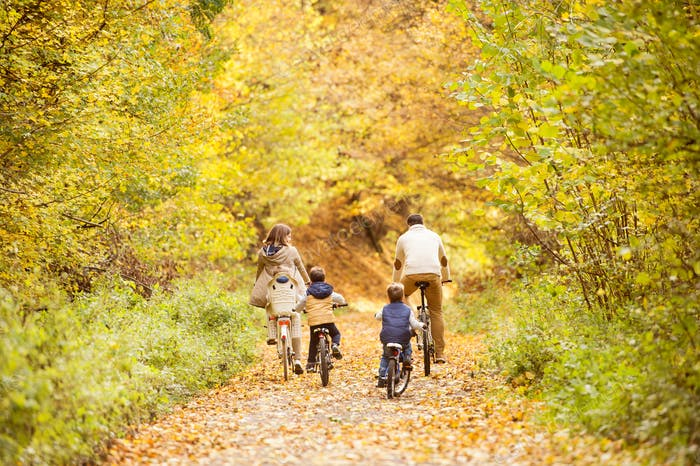 Thumbnail for Young family in warm clothes cycling in autumn park