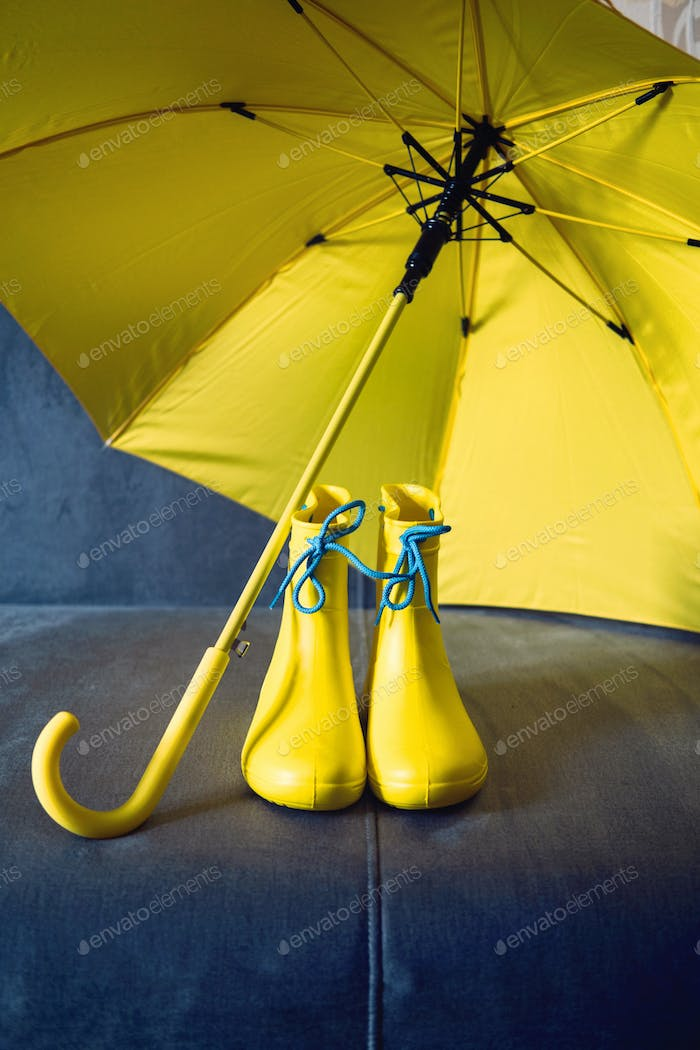 Rainy Mood, outfit for rainy day. Blue raincoat, yellow rubber boots and umbrella on a gray sofa