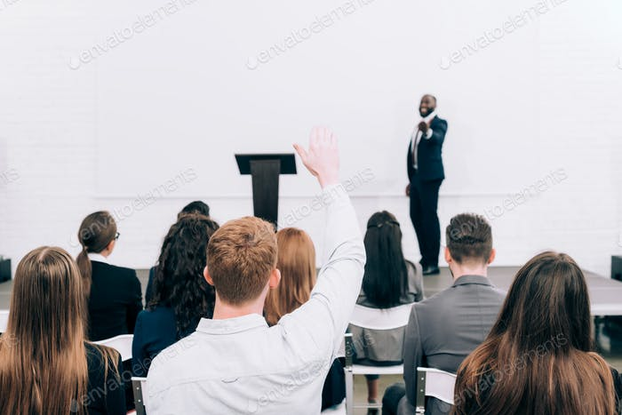 back view of listener raising hand during seminar in conference hall