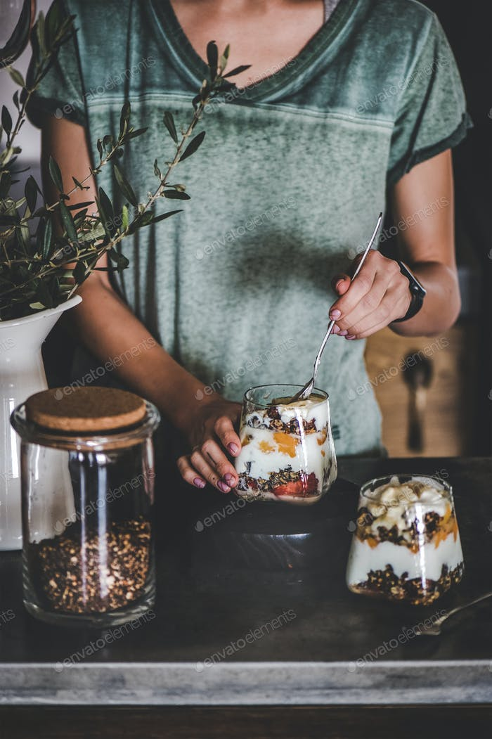 Woman having healthy breakfast with yogurt, granola, fruits in glass