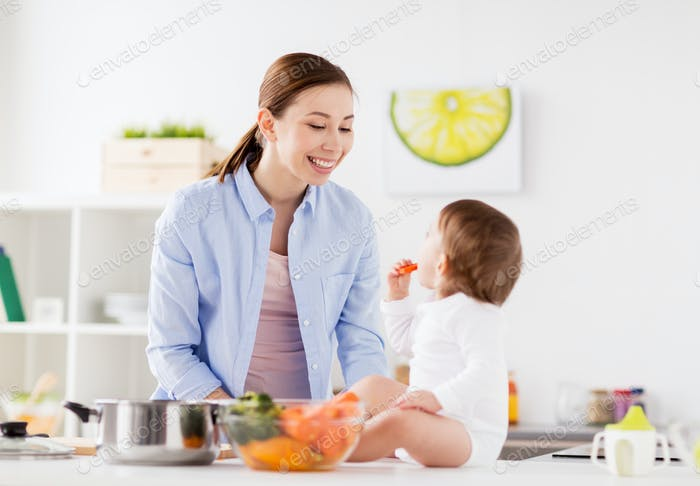 happy mother and baby eating at home kitchen
