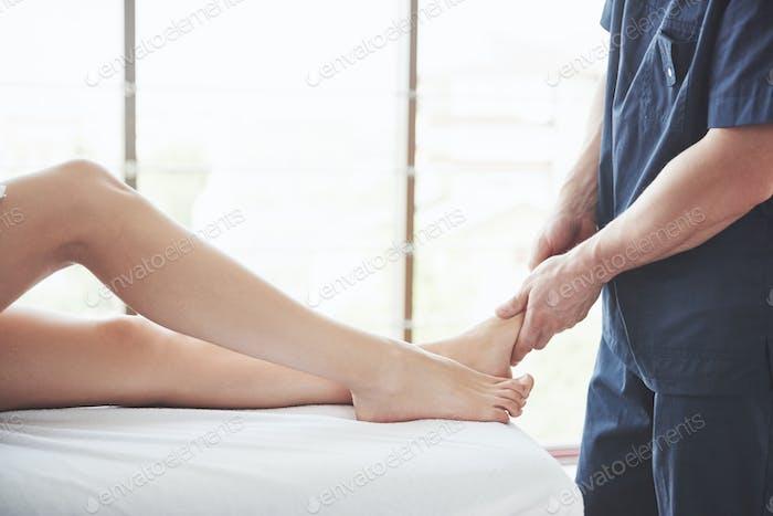 Close-up of massage therapist massaging beautiful female leg