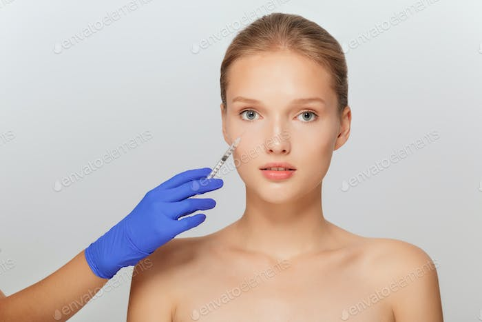 Portrait of young attractive woman getting beauty injection in e