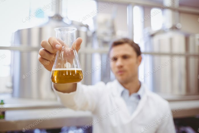 Thoughtful scientist holding a beaker in the factory