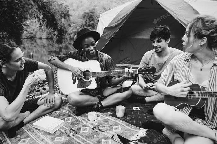 Group of young adult friends in camp site playing guitar and uke
