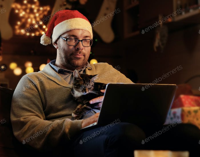 A man  in Santa's New Year hat holds a cat and working with laptop.