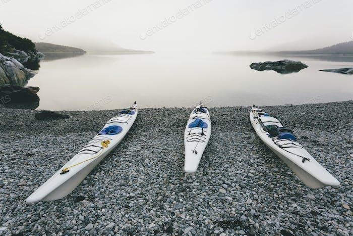 Three sea kayaks pulled up into shoreline of Muir Inlet, Alaska.
