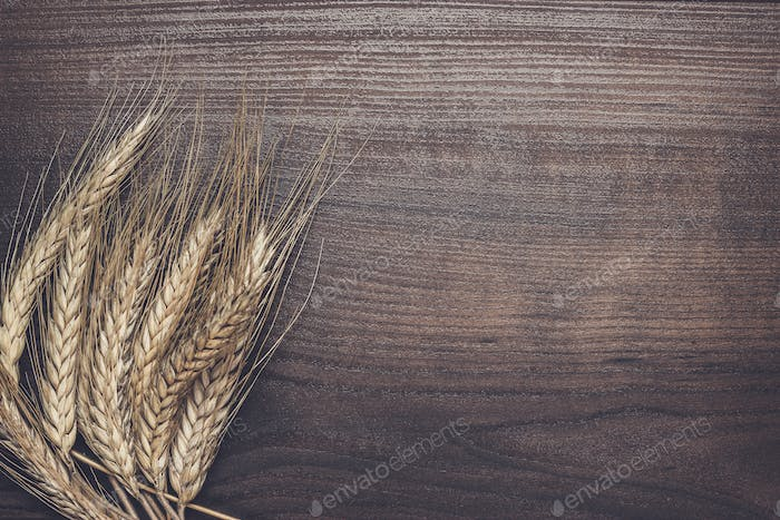 ears of rye over wooden background