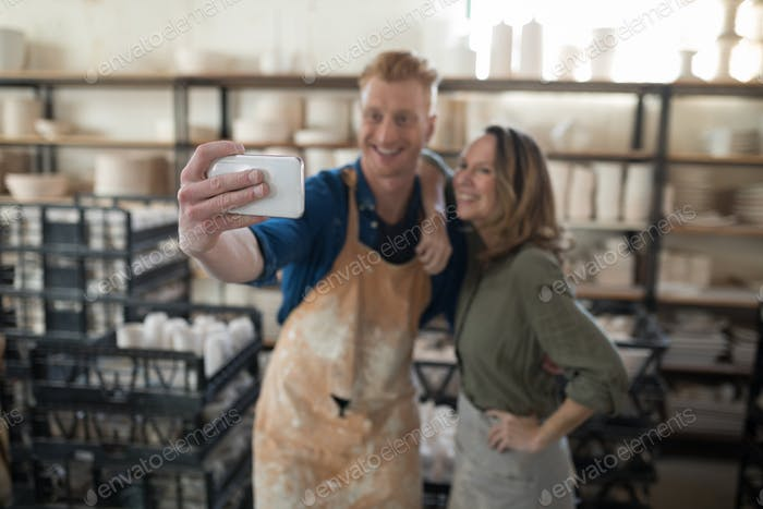Male and female potter taking selfie with mobile phone