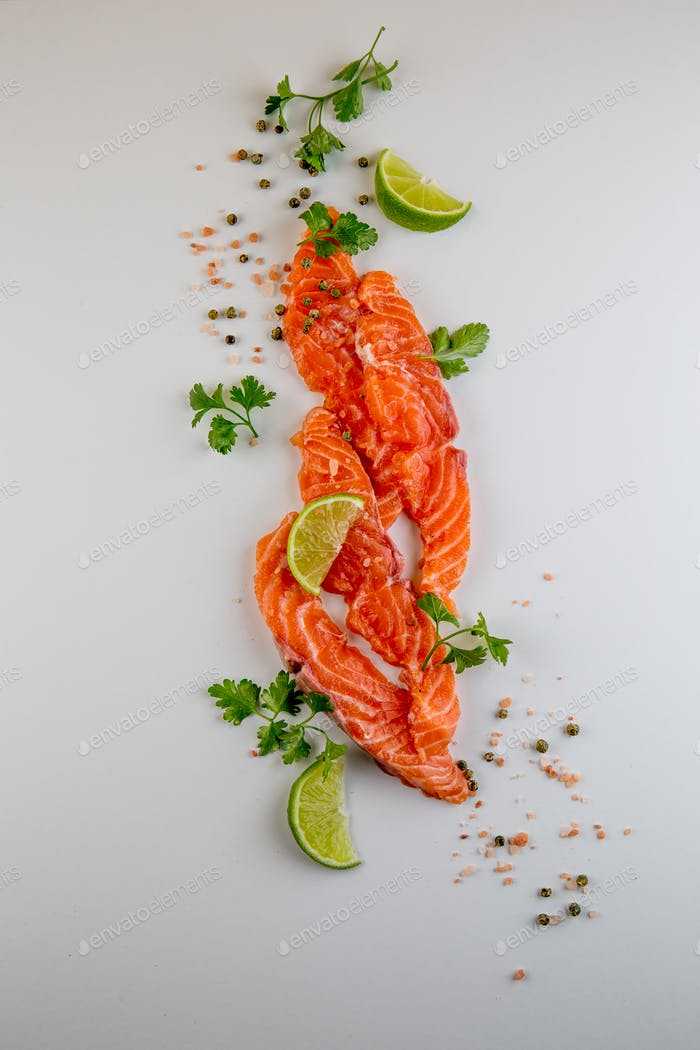 Fresh salmon slices and spices on white background.