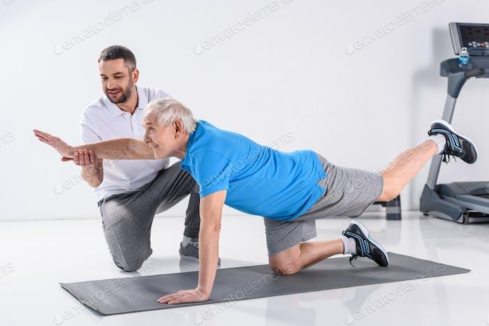 rehabilitation therapist helping smiling senior man exercising on mat