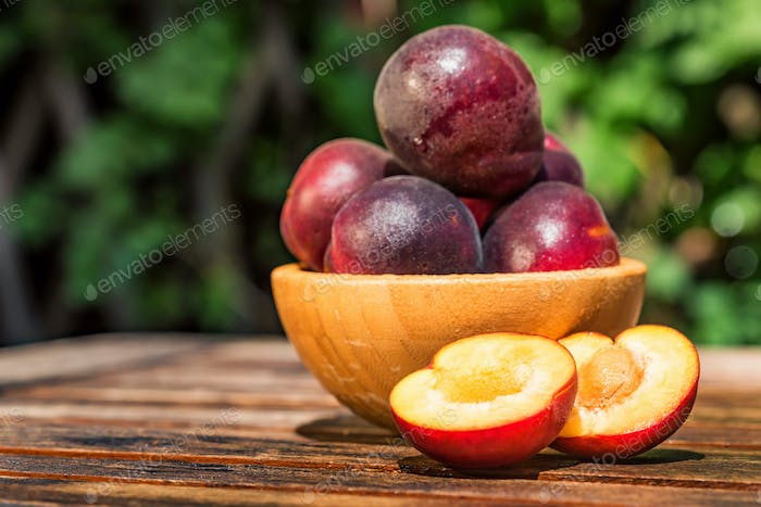 Pluot, mix of plum and apricot in wooden bowl