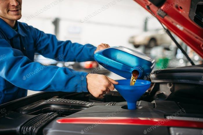 Techniker gießt neues Öl in den Automotor