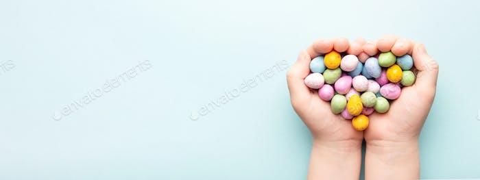 Child Hands Holding Easter Egg Candies. Banner.